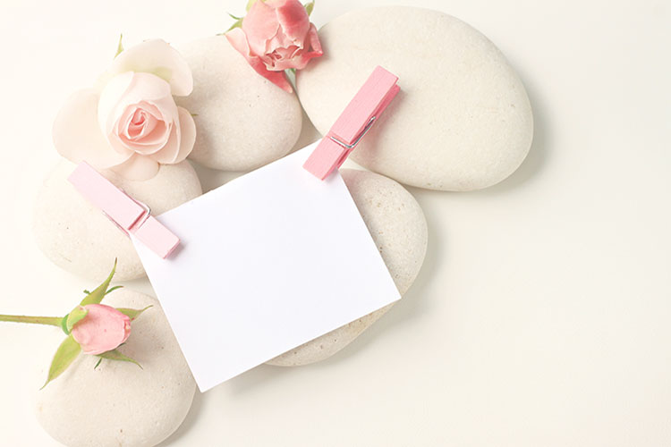 Image of several smooth stones and flowers with a blank white card atop.