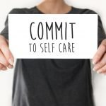 "A person holding a card that says ""Commit To Self Care"""